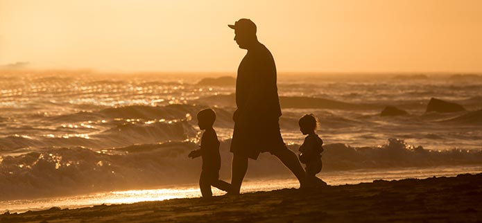 Kids and father silhouette at beach at sunset.